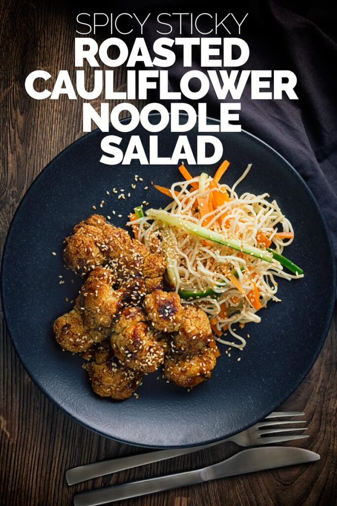 Tall overhead image of spicy roasted cauliflower florets with a noodle salad side dish on a black plate with text