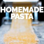 Fresh egg pasta tagliatelle being made with a pasta machine with narrow DOF