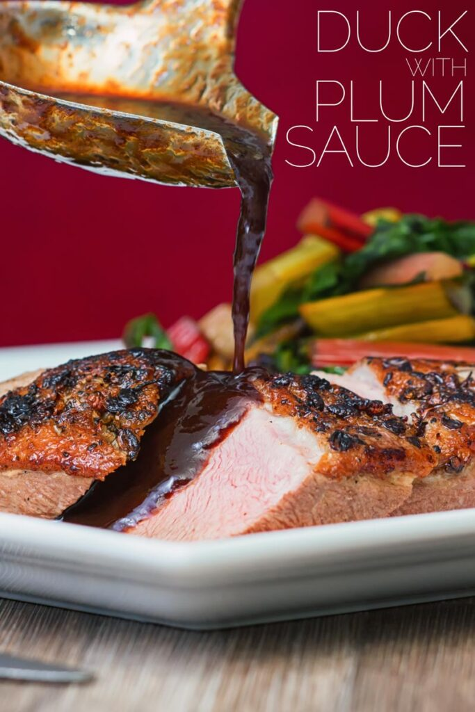 Portrait image of duck with plum sauce with the plum sauce being poured from a ladle