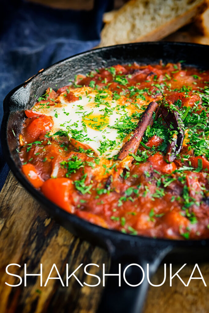 Portrait image of Shakshouka served in a cast iron skillet featuring baked eggs served with wholegrain bread with text