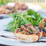 Portrait wide angle image of grilled stuffed mushrooms on a white plate with a rocket side salad with a garden scene in the background with text