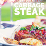 Portrait image of grilled balsamic cabbage steaks served with a tomato salsa and seared potatoes on a white plate adn two glasses of wine in a garden setting with text
