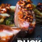 Close up portrait image of pan fried glazed duck breast with walnuts and cabbage in a balsamic sauce on a black plate with text