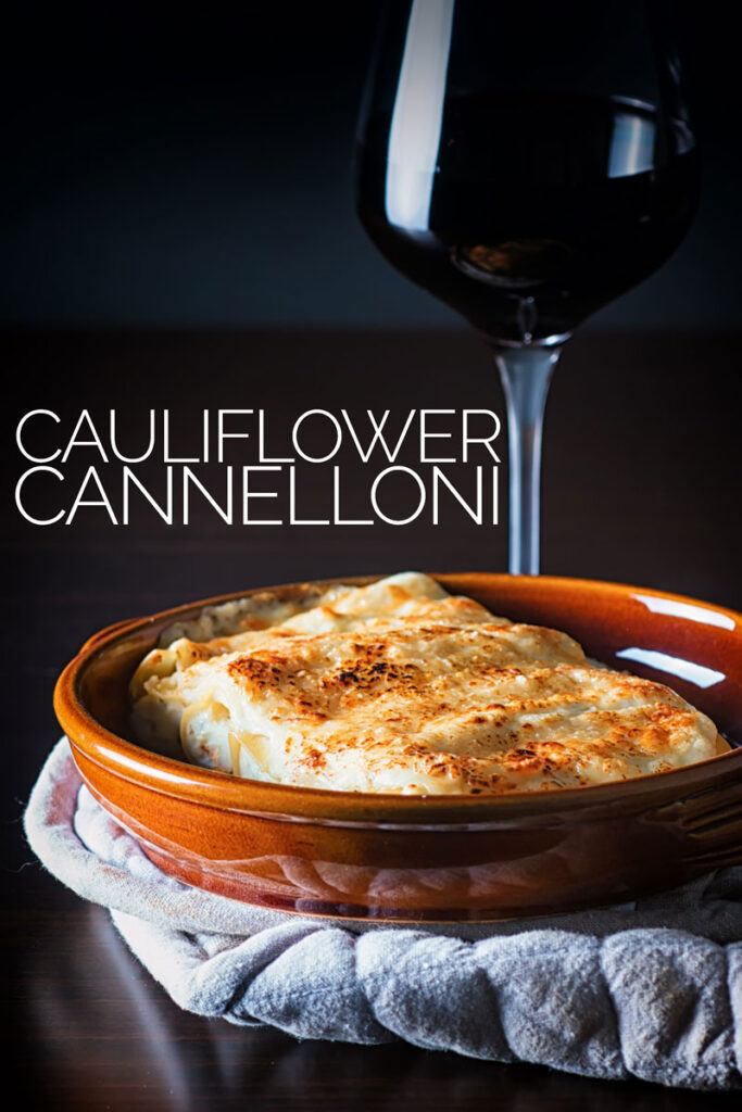 Portrait image of cauliflower cannelloni with a cheesy topping served in an earthenware bowl against a dark backdrop with text