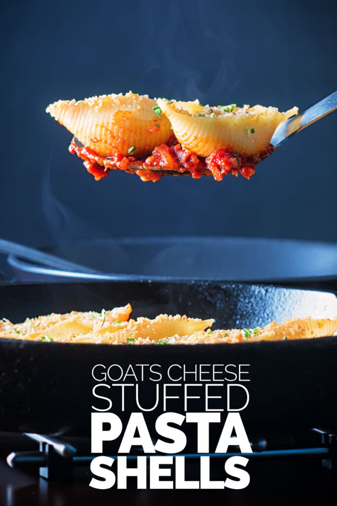Portrait image of Goats Cheese Stuffed Pasta Shells served in a cast iron pan with two steaming pasta shells on a serving spoon with text