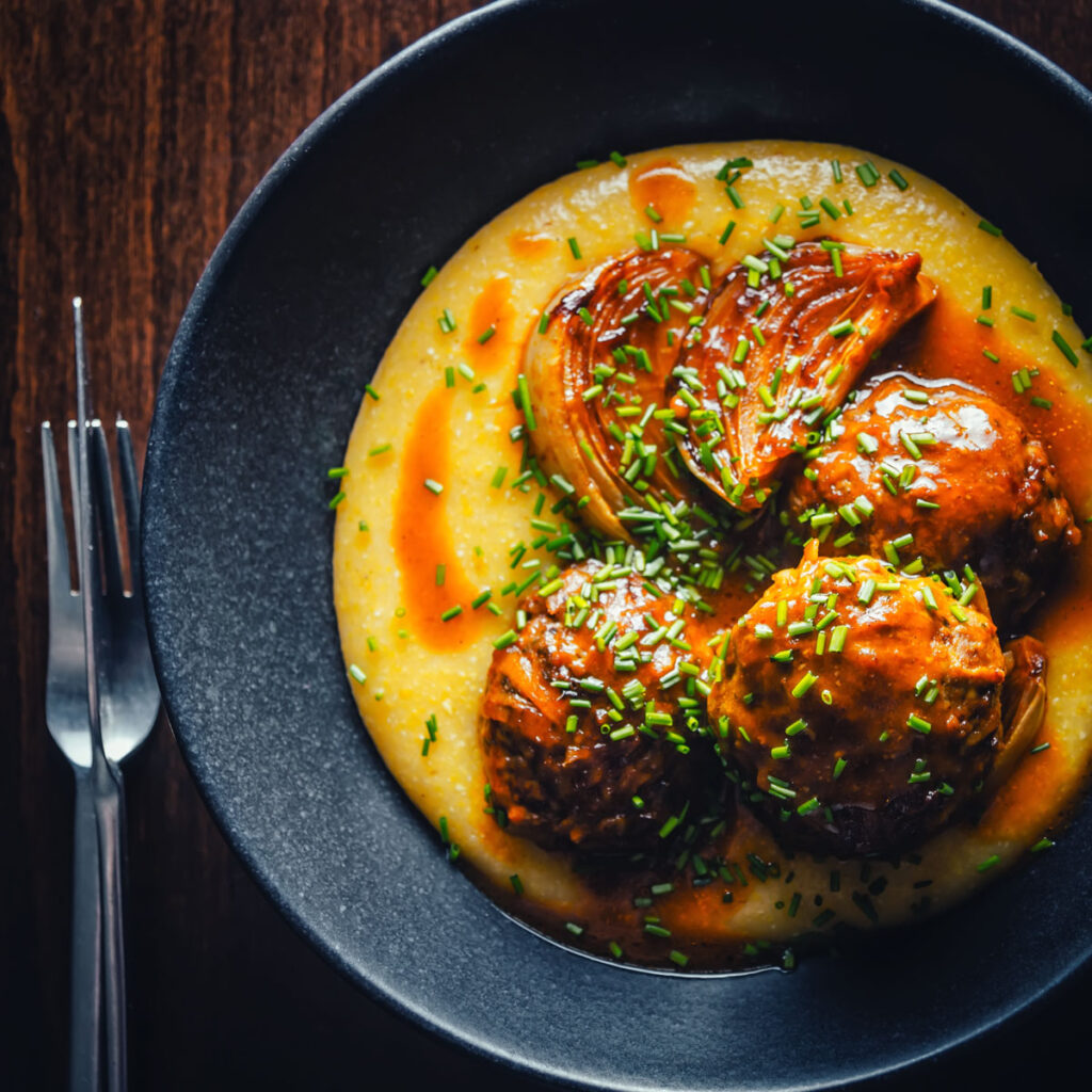 Let's set spaghetti aside and rock some pork meatballs in a beer sauce on a cheesy polenta base for a change!