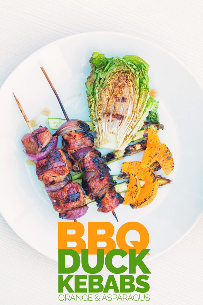 Portrait overhead image of BBQ duck kebabs served on a white plate with grilled lettuce, asparagus and seared orange segments with text
