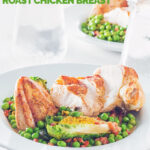 Portrait image of petits pois a la Francaise served in a white bowl with a sliced roast chicken breast on a bright backdrop with iced water with text