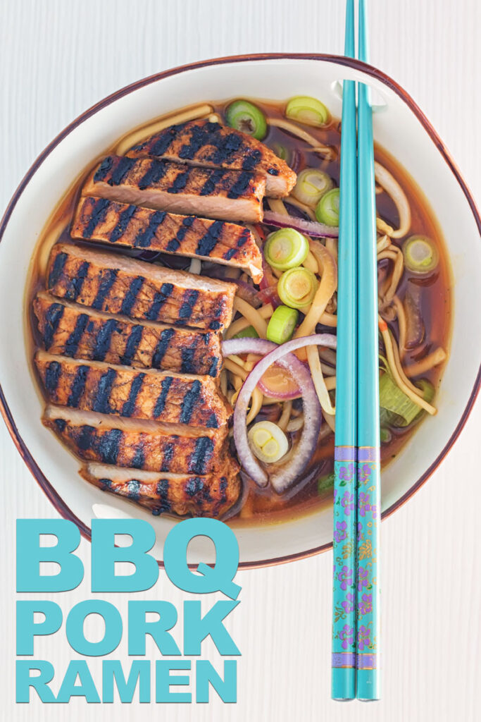 Overhead portrait image of a spicy pork ramen noodle soup served in a bowl with turquoise chopsticks with text