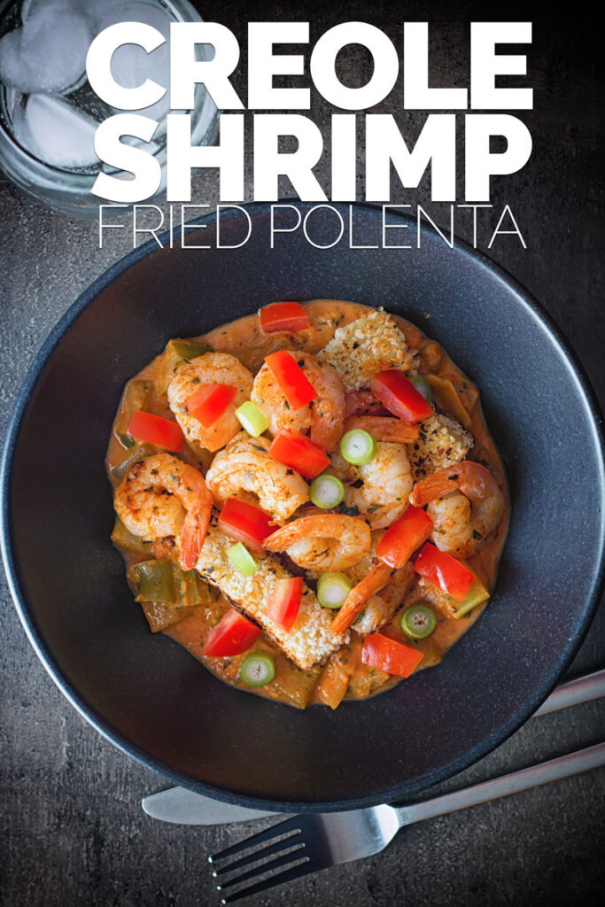 Overhead portrait image of shrimp creole with fried polenta with fried polenta in a black bowl with text