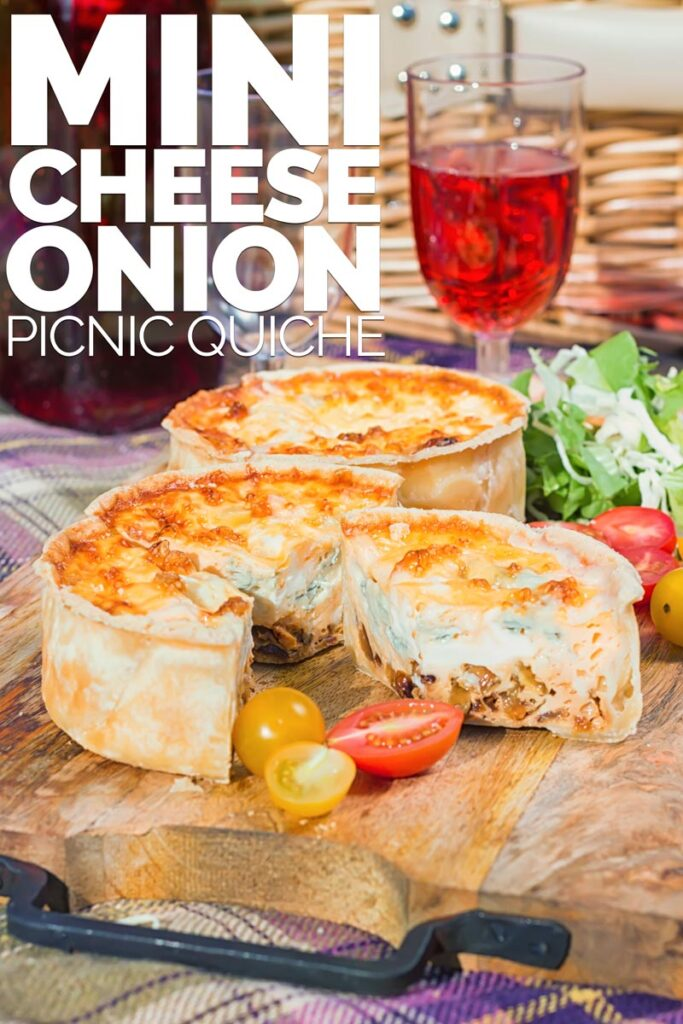 Portrait image of two mini cheese and onion quiche with one mini quiche cut open on a wooden chopping board in a picnic setting with text