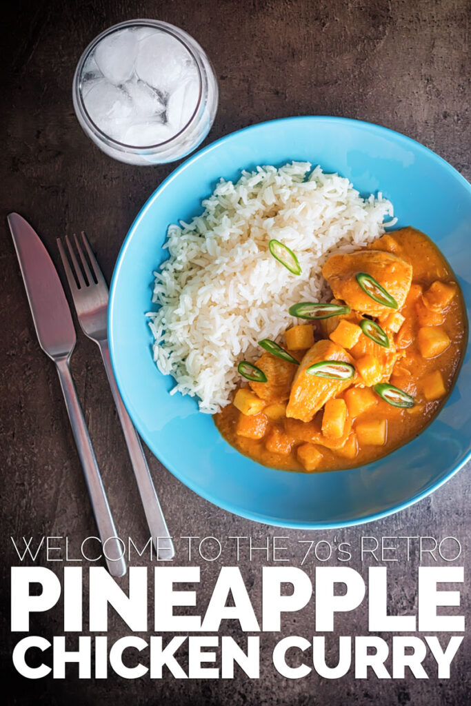 Tall overhead image of a colourful fruity pineapple chicken curry served in a blue bowl with white basmati rice set against a dark backdrop with text