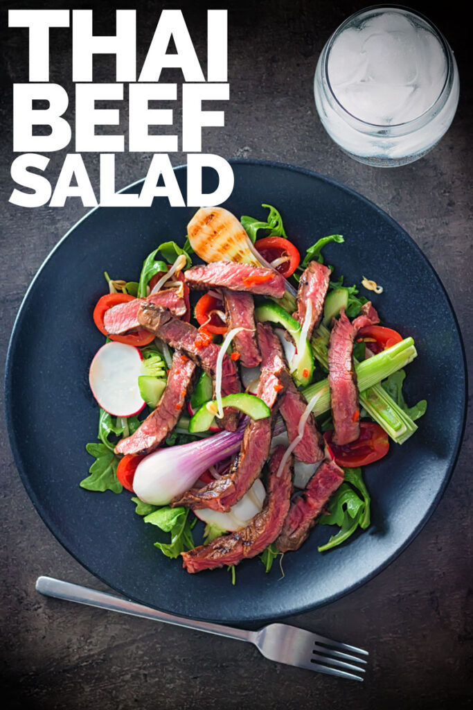 Portrait overhead image of Thai beef salad featuring rare steak, grilled purple spring onions and radishes with text