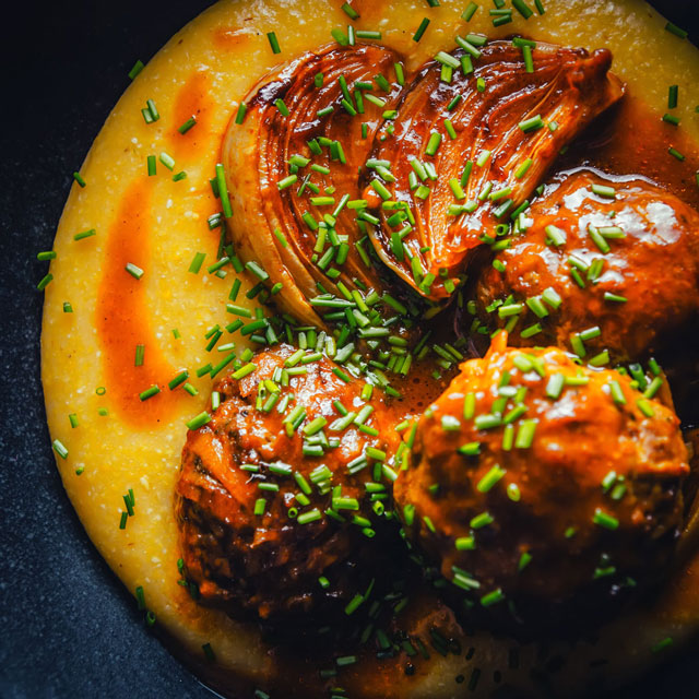 Let's set spaghetti aside and rock some braised pork meatballs in a beer sauce on a super cheesy polenta base for a change!