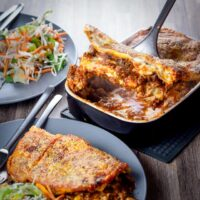 A classic baked lasagne is a thing of great beauty, unctuous rich beef ragu, a luxurious white sauce and layers of pasta with a cheesy topping.