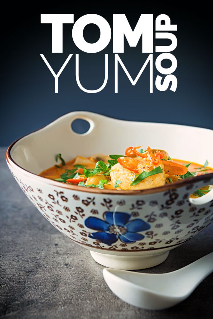 Portrait image of a Tom Yum Soup served in an Asian style soup bowl decorated with a blue flower in a dark setting with text
