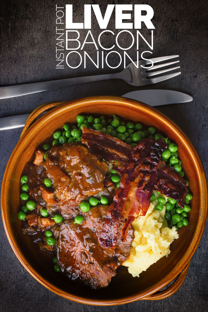 Portrait overhead image of liver and onions with crispy bacon, mashed potatoes and peas and onion gravy served in an earthenware bowl with text