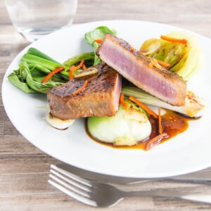 This glorious honey and soy glazed tuna steak is pimped up with a bit of chili and seared rather than cooked, it is served with some garlic braised pak choi and spring onions.