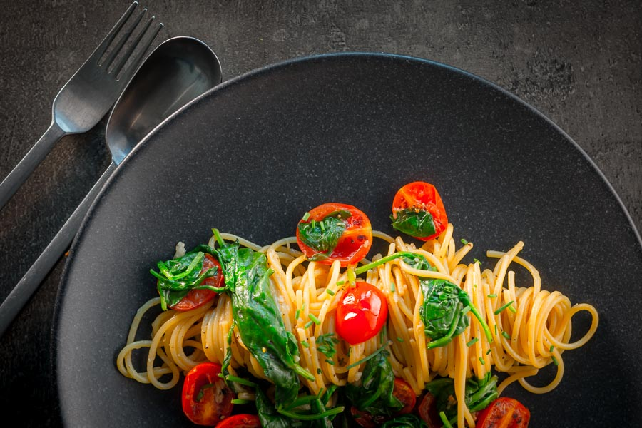 Landscape overhead image of Garlic pasta served in swirl on a dark plate with seared tomatoes and wilted spinach