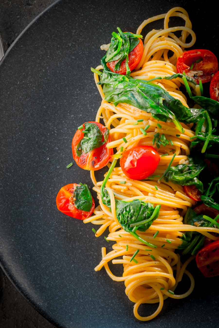 Portrait image of Garlic pasta served in swirl on a dark plate with seared tomatoes and wilted spinach