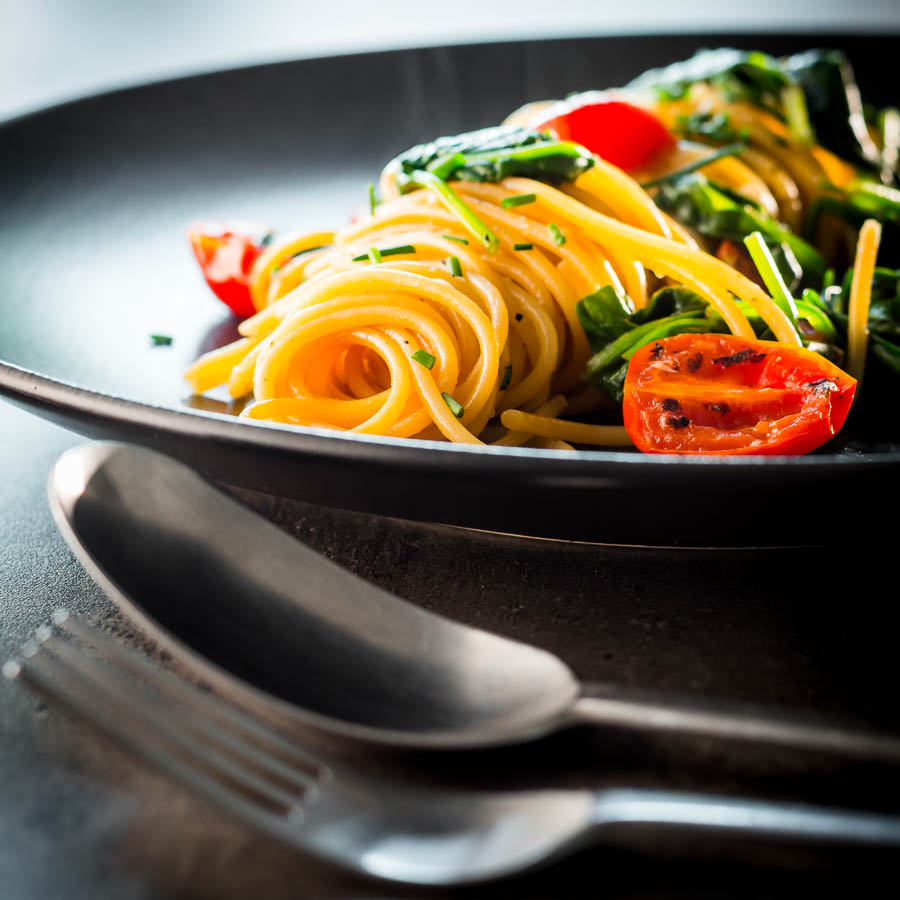 Square image of Garlic pasta served in swirl on a dark plate with seared tomatoes and wilted spinach