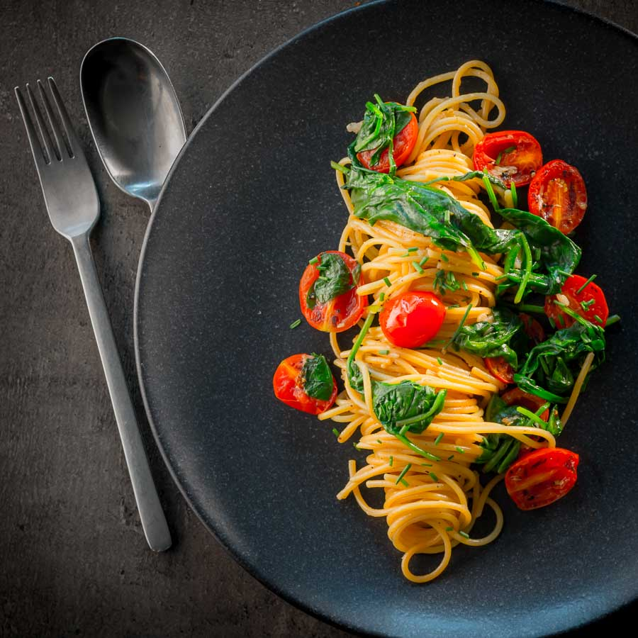 Square overhead image of Garlic pasta served in swirl on a dark plate with seared tomatoes and wilted spinach