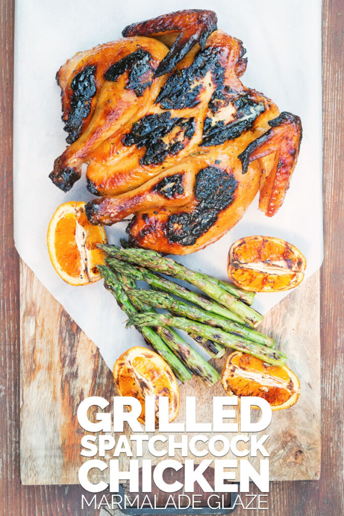 Portrait image of a Grilled Spatchcock Chicken served on a wooden chopping board with asparagus and grilled orange segments with Text