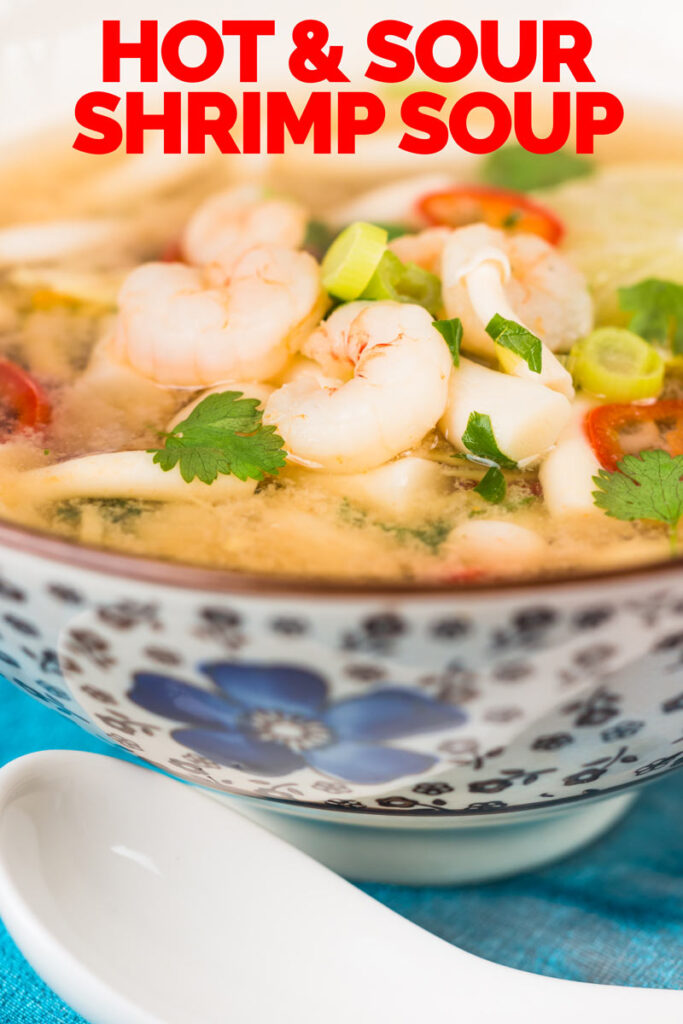 Close up tall image of a hot and sour shrimp soup with mushrooms and chili and lemon in a clear broth in an Asian style bowl decorated with a blue flower with text