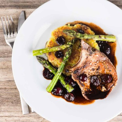 Simply pan fried pork chops are served with a simple potato rosti, some balsamic cherries and asparagus for an old school but delightful meal!