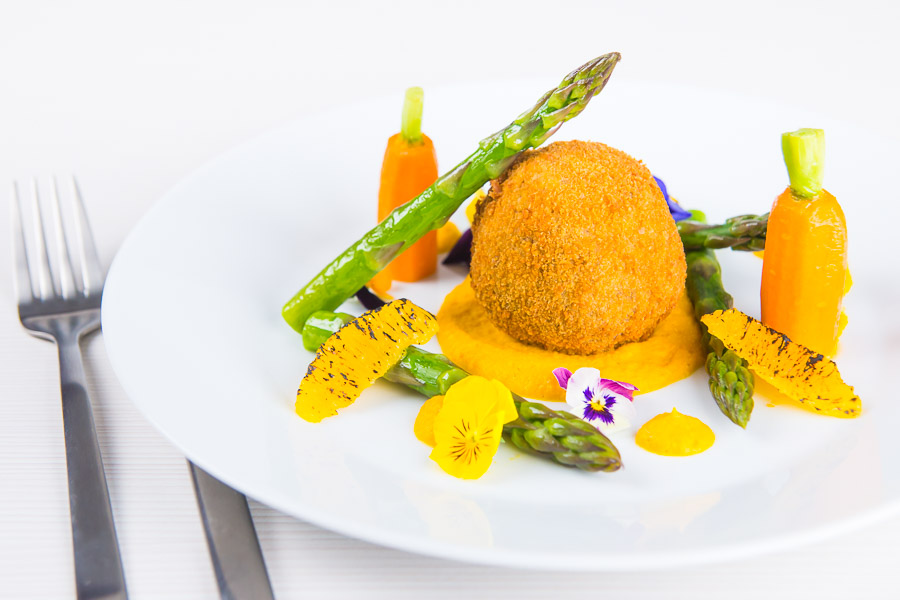 These confit duck leg bonbons are at the centre of a surprisingly light and wonderfully fancy meal featuring an orange and cumin puree and asparagus.