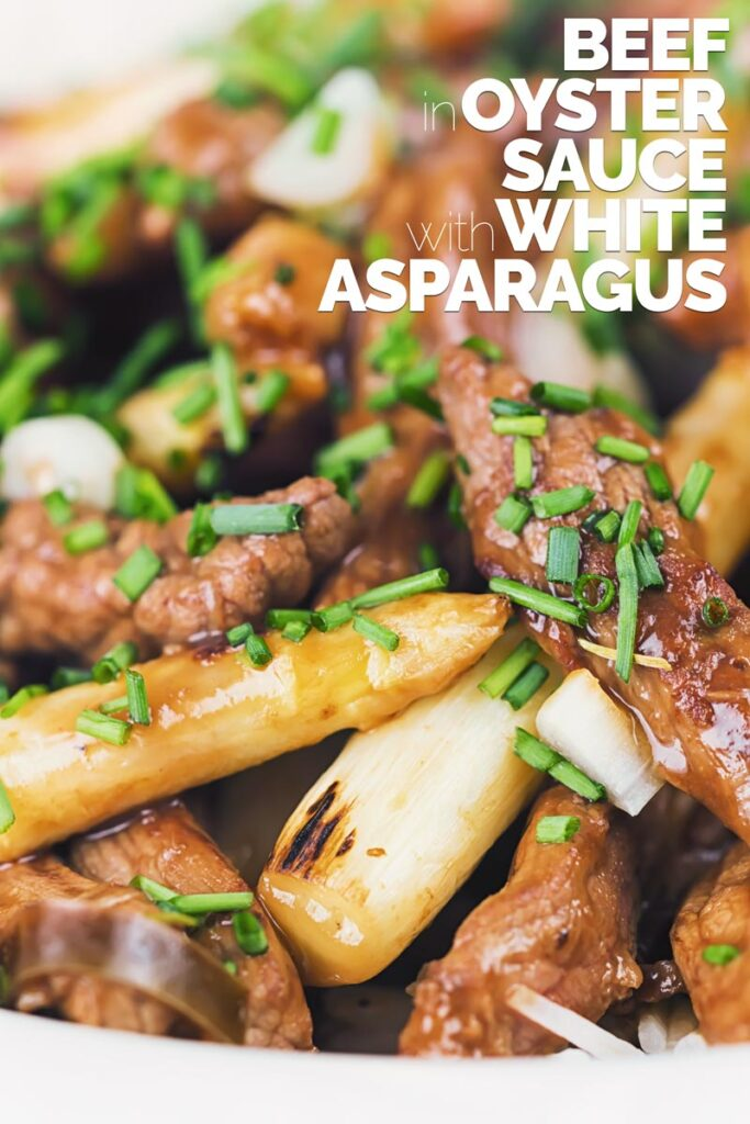 Tall close up image of beef with oyster sauce and white asparagus in a white bowl with herbed rice with text