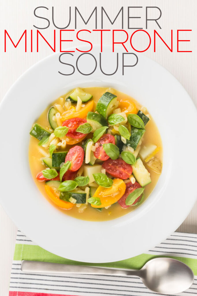 Portrait overhead image of a summer minestrone soup featuring courgette and tomato in a light broth with basil leaves and small pasta in a white bowl with text