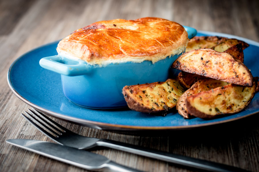 Landscape image of a Chicken and mushroom pie in a blue pot pie pot with potato wedges