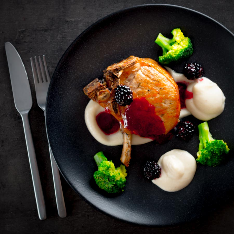 Pork chops are served along side a silky Jerusalem artichoke puree with a cider and blackberry sauce on this perfect late summer early autumn dish.