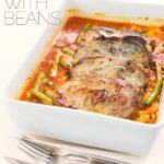 Roast pork chops are always fab and these boneless pork blade or Boston butt chops are roasted on a bed of green beans and white beans in a tomato sauce.