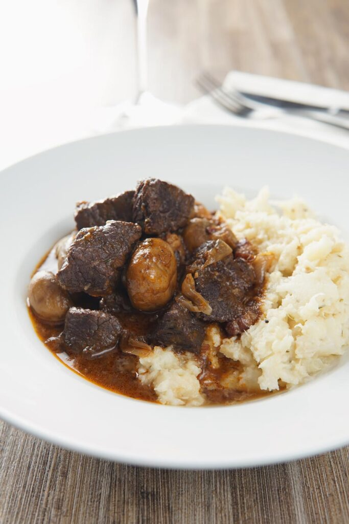 Portrait image of Beef Bourguignon served with a celeriac mash in a shallow white bowl