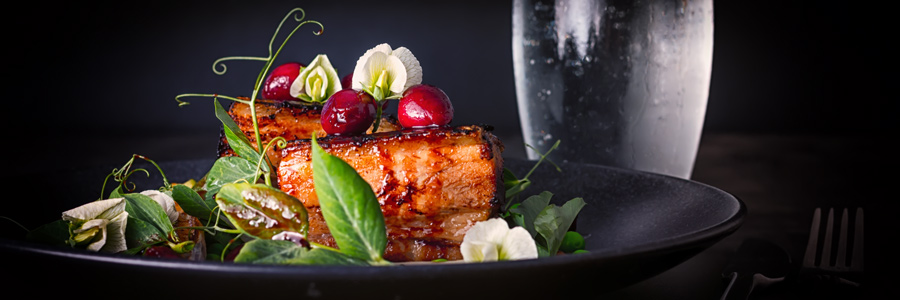 Pressed pork belly served with pea shoots and cherries served on a black plate against a dark background.