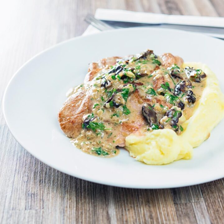 Pork with prunes in a creamy sauce served over mashed potatoes