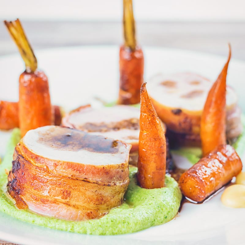 Square image of Bacon wrapped Baked Pork Tenderloin slice on a broccoli puree with carrots