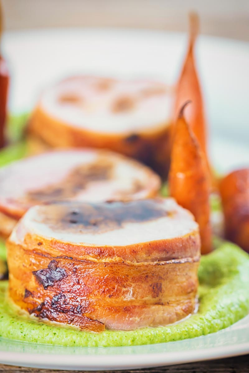 Portrait image of Bacon wrapped Baked Pork Tenderloin slice on a broccoli puree with carrots