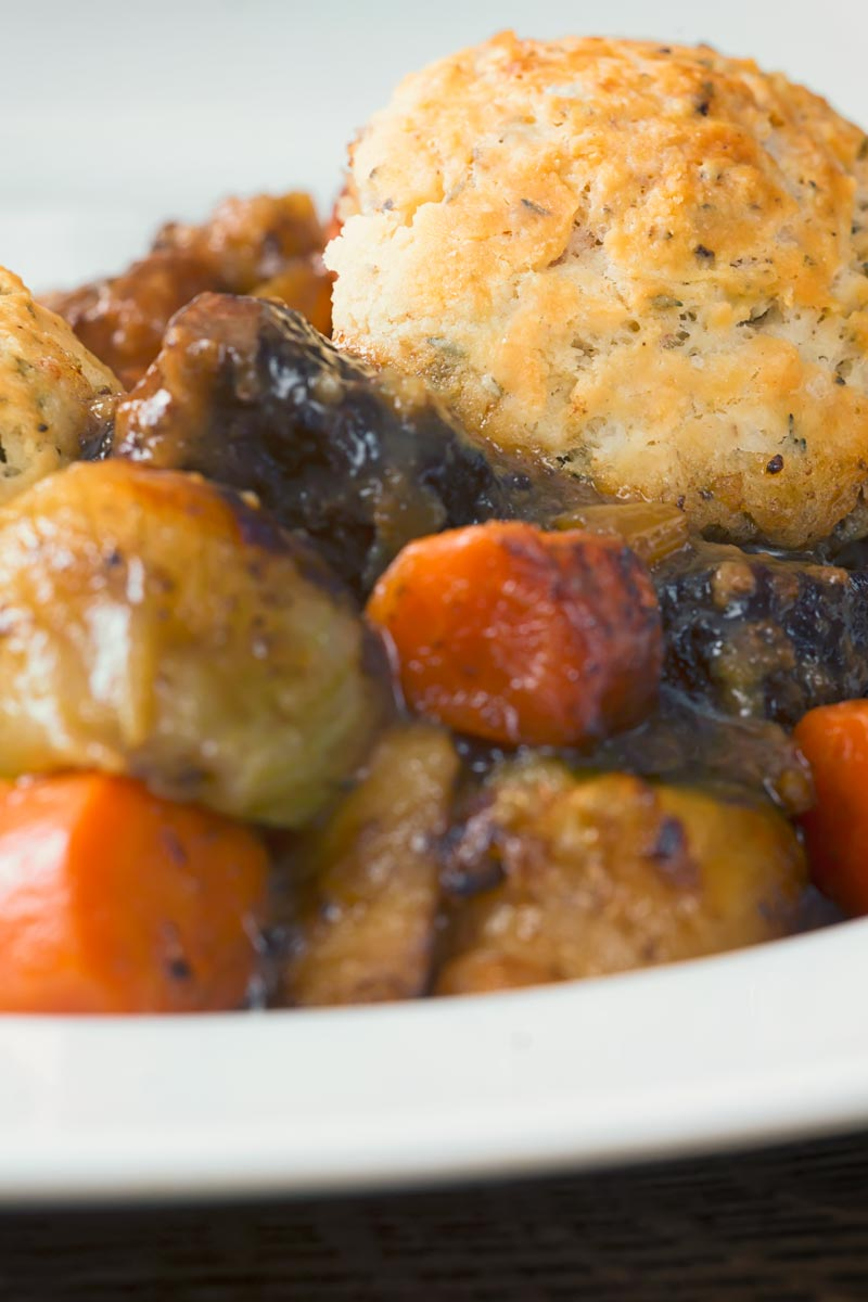 Portrait image of a suet dumpling in a slow cooked beef stew