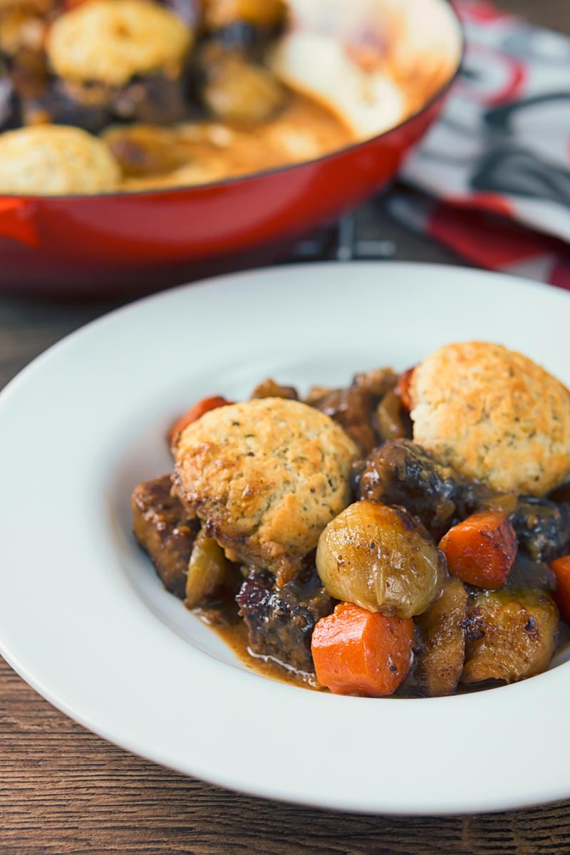 Portrait image of a slow cooked beef stew with suet dumplings in a white bowl
