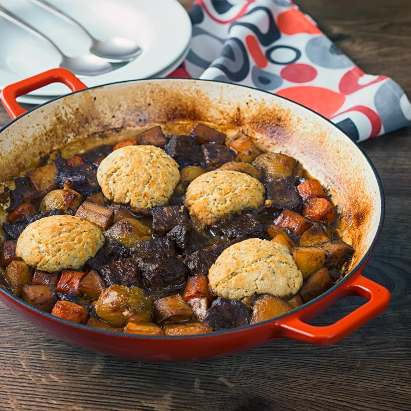 Square image of a slow cooked beef stew with suet dumplings in a red cast iron enameled pan