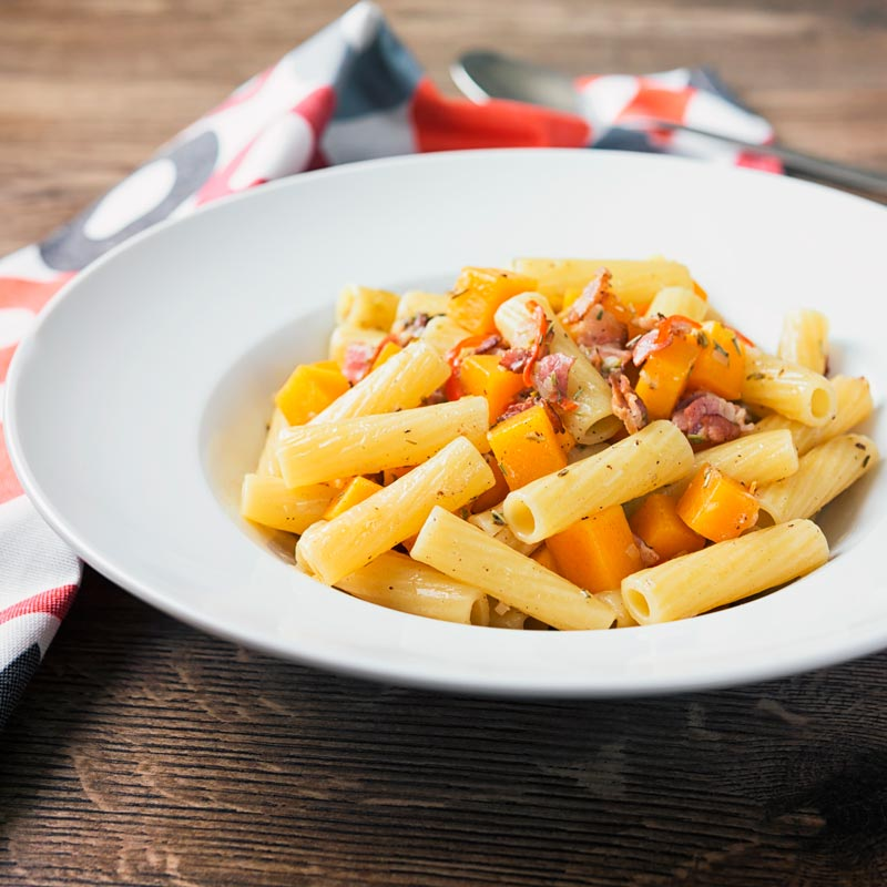 Square image of butternut squash pasta with bacon and chili in a white bowl on a wooden backdrop