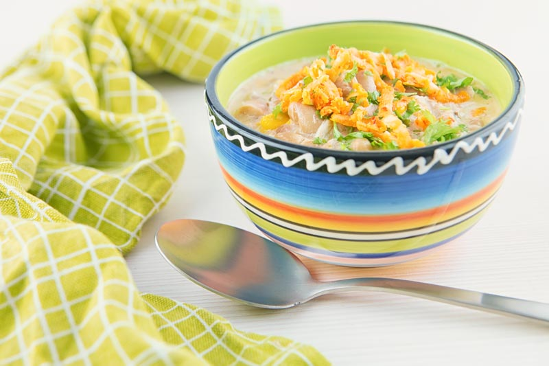 A landscape image of a white chili chicken topped with red Leicester cheese in a bright colourful bowl
