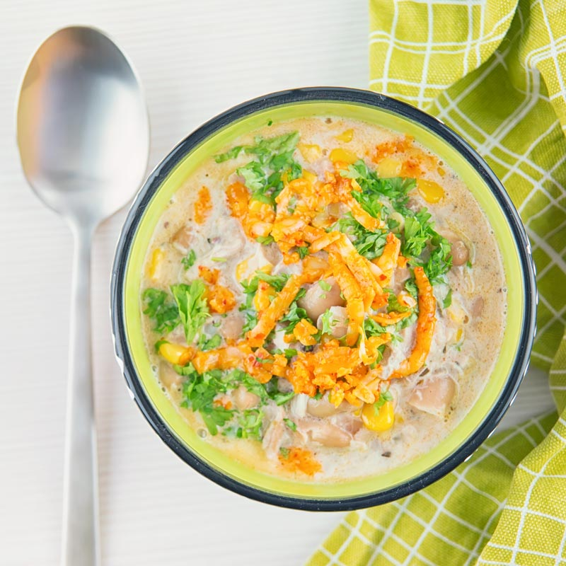 A square image taken from above of a white chili chicken topped with red Leicester cheese in a bright colourful bowl