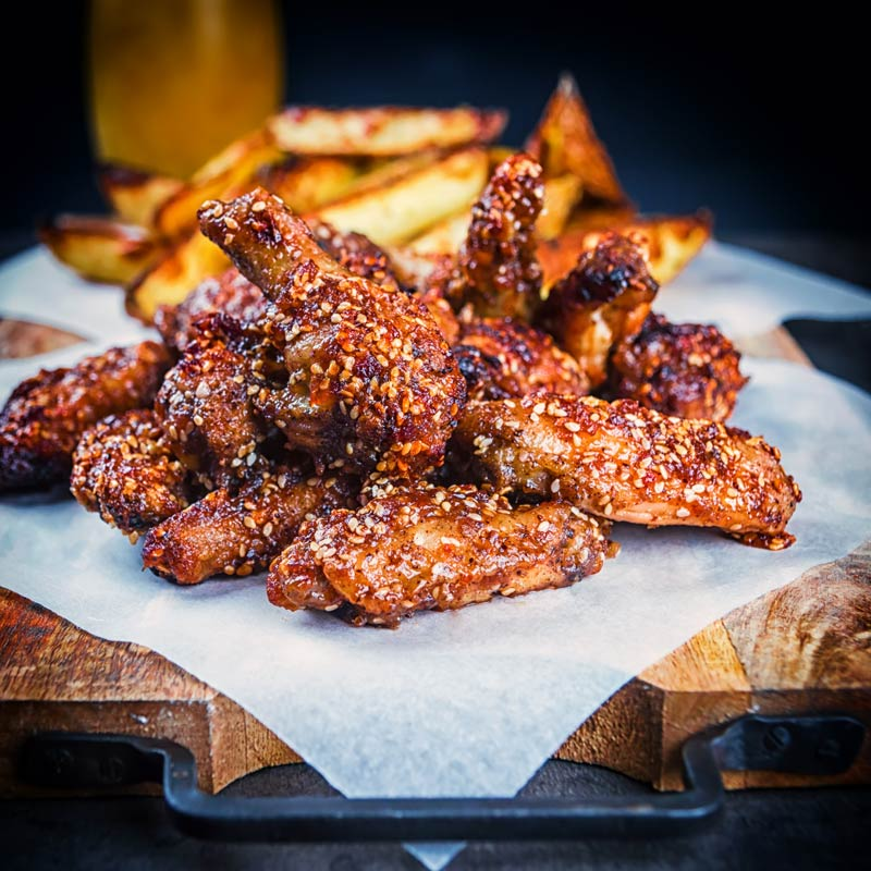 Square image of sticky spicy glazed buffalo chicken wings on a board with potato wedges and a beer