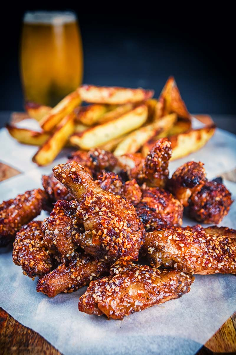 Portrait image of sticky spicy glazed buffalo chicken wings on a board with potato wedges and a beer