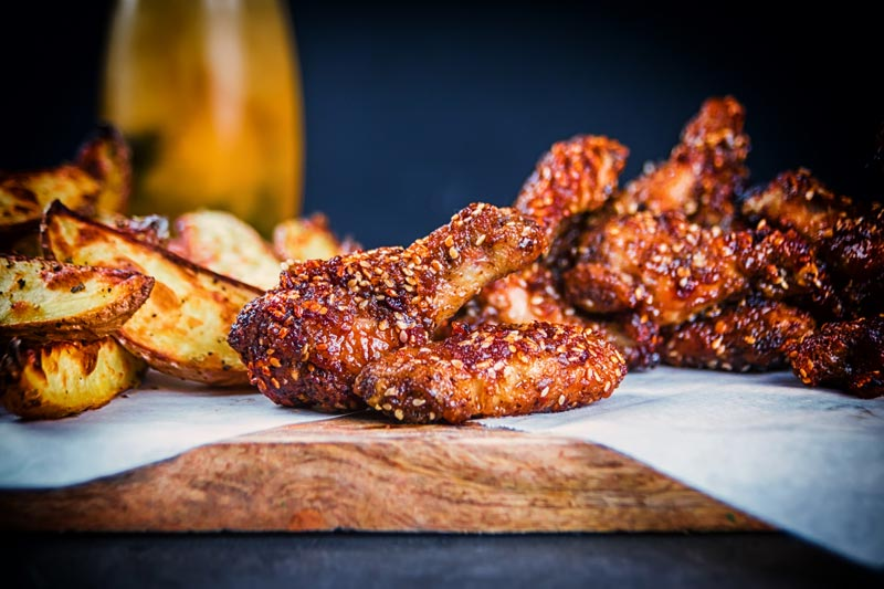 Landscape image of sticky spicy glazed buffalo chicken wings on a board with potato wedges and a beer