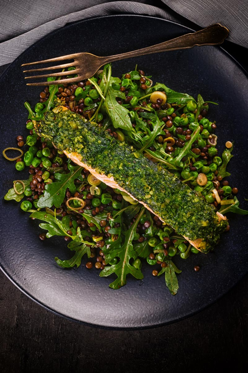 Tall image taken from above of baked salmon filllet with a green herby crust on a lentil salad against a dark backdrop